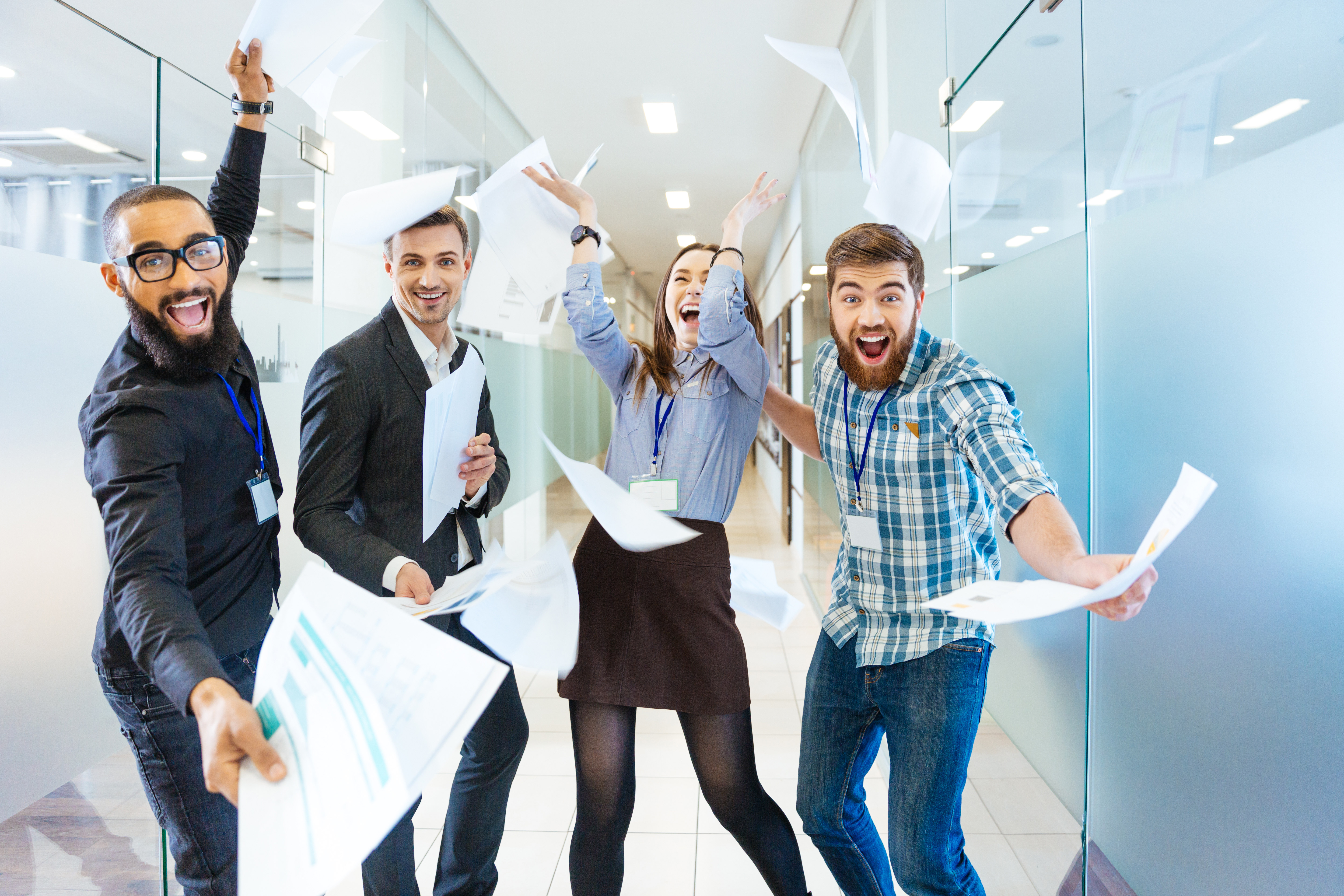 Group of joyful excited business people throwing papers and having fun